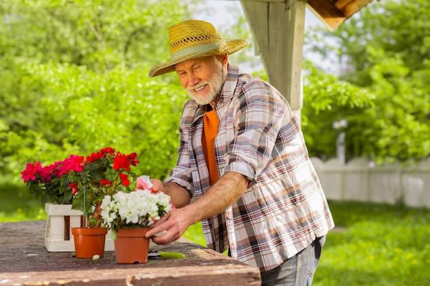 Près de la maison d'été. homme âgé barbu vivant dans une maison d'été souriant tout en arrosant les plantes