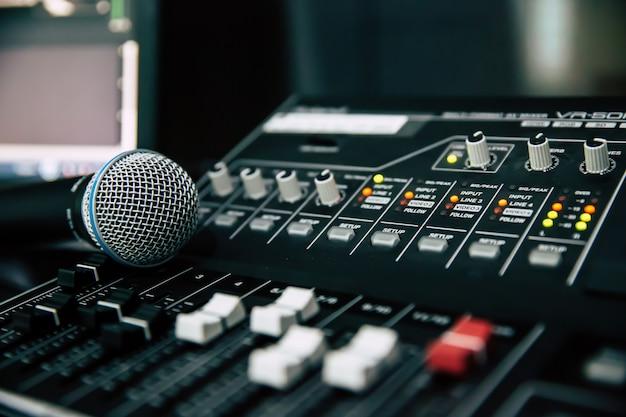 De près, le microphone est placé sur la table de mixage audio professionnelle.