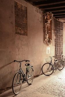 Près de la vieille maison dans une arche il y a plusieurs vieux vélos près du mur