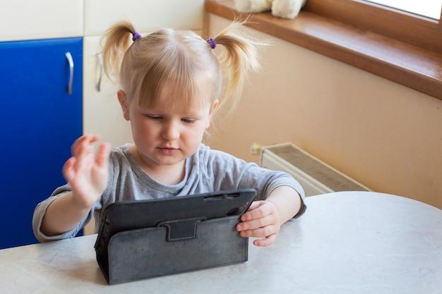 Preschool caucasian little girl learning en ligne à la maison.