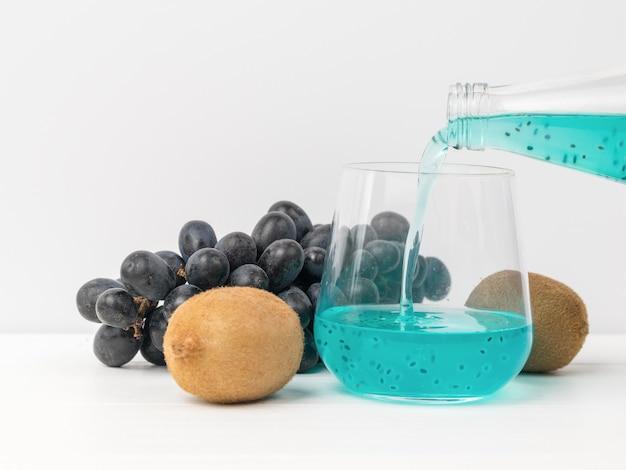 La présence d'un cocktail aux graines de basilic d'une bouteille à un verre à la surface des raisins
