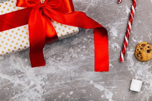 Présent boîte avec ruban rouge se trouve sur le sol gris avec des biscuits de noël, des pains d'épice et des bonbons blancs rouges