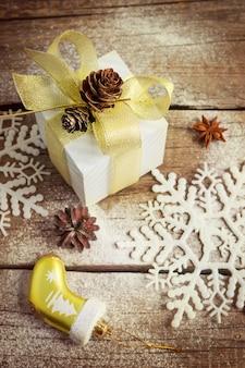 Présent dans un emballage de fête avec un arc, des flocons de neige et une pomme de pin en or