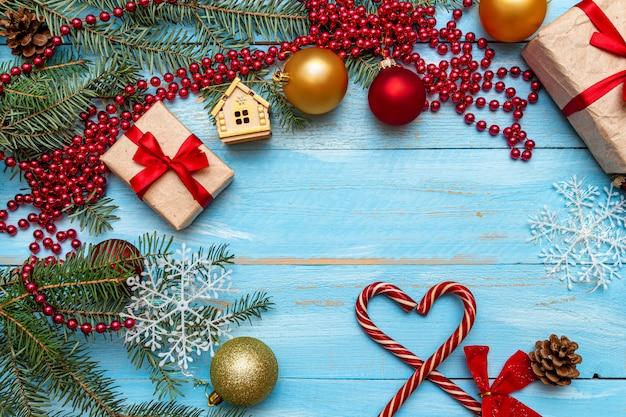 Présent avec noeud rouge et décoration de noël sur le fond en bois peint bleu