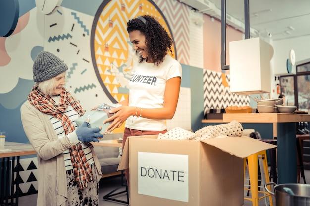 Présent de nous. femme afro-américaine positive souriant tout en donnant un beau cadeau à une femme sans-abri