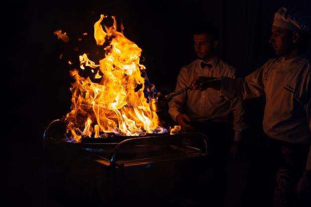 Présentation du feu et émission de cuisine à la réception de mariage, le chef cuisine de la viande délicieuse