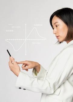 Présentation graphique numérique futuriste par une femme d'affaires en costume blanc