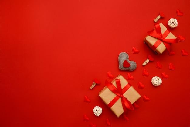 Présente avec un arc rouge et une décoration valentin sur rouge avec des confettis coeur. style plat. saint valentin