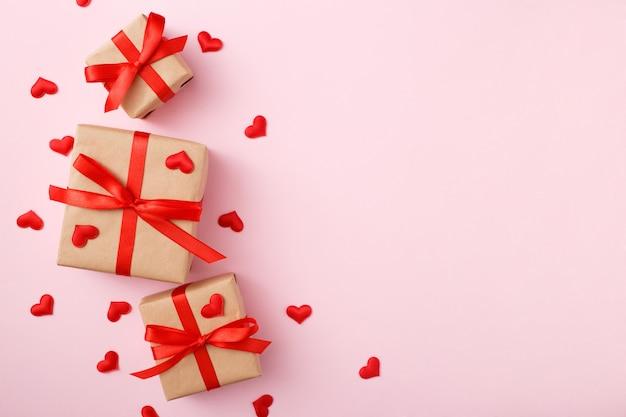 Présente avec un arc rouge sur fond rose avec des confettis coeur. style plat. concept de la saint-valentin