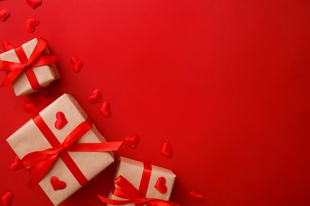 Présente avec un arc rouge sur rouge avec des confettis coeur. style plat. saint valentin