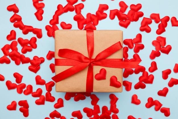 Présenter avec un arc rouge sur bleu avec des confettis coeur. style plat. saint valentin