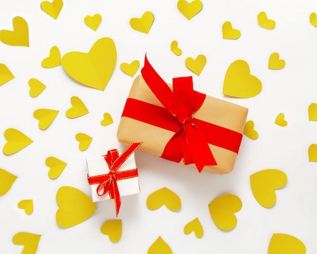 Présenter la boîte cadeau à plat. vue de dessus des décorations de la saint-valentin. boîte cadeau ruban rouge, coeurs verts. bannière de joyeux anniversaire