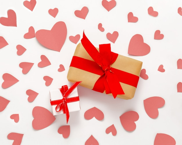 Présenter la boîte cadeau à plat. vue de dessus des décorations de la saint-valentin. coffret cadeau, ruban rouge, coeurs roses. bannière de joyeux anniversaire