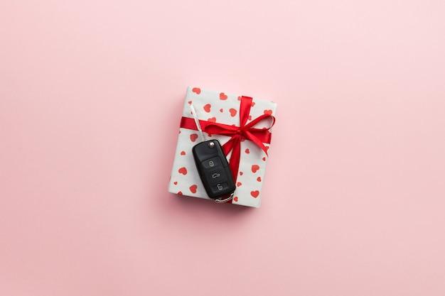 Présenter la boîte avec un ruban rouge noeud, coeur et clé de voiture sur fond rose.