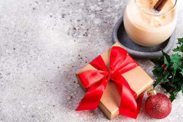 Présenter la boîte avec des rubans rouges, une boule, des branches de lait de poule et de baies de houx sur une table en pierre, un fond plat. noël et nouvel an
