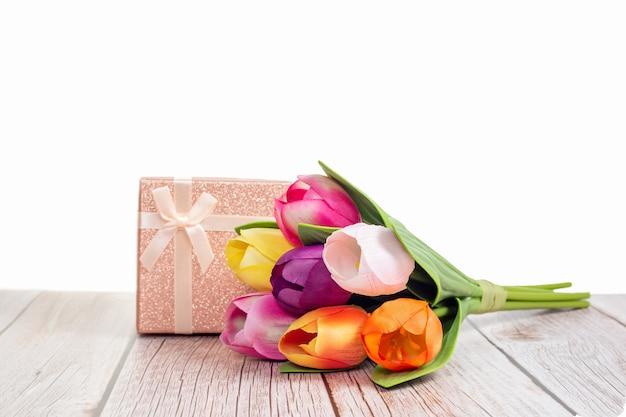Présenter la boîte et les tulipes sur une table rustique en bois avec un fond blanc avec un espace pour le texte.