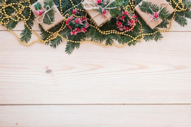 Présenter des boîtes sur une branche de sapin décorée et des perles