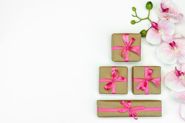 Présenter des boîtes avec ruban rose avec des fleurs d'orchidées sur fond blanc