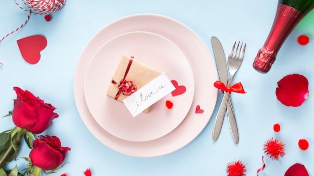 Présenter avec du papier sur une assiette près des couverts, des roses et une bouteille de champagne