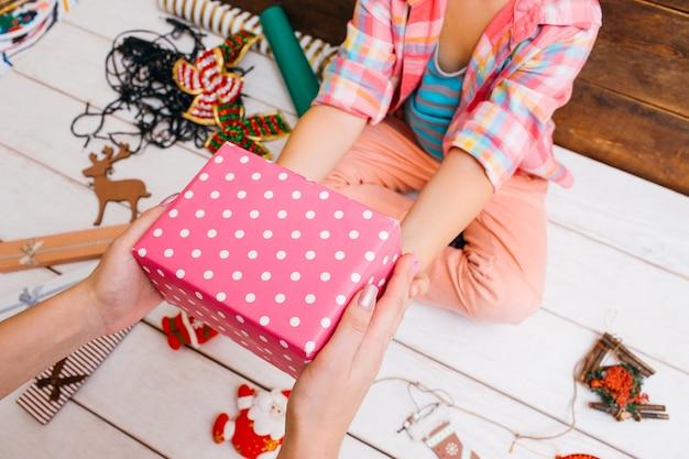 Présenter une fille donnant une boîte cadeau rose à sa mère