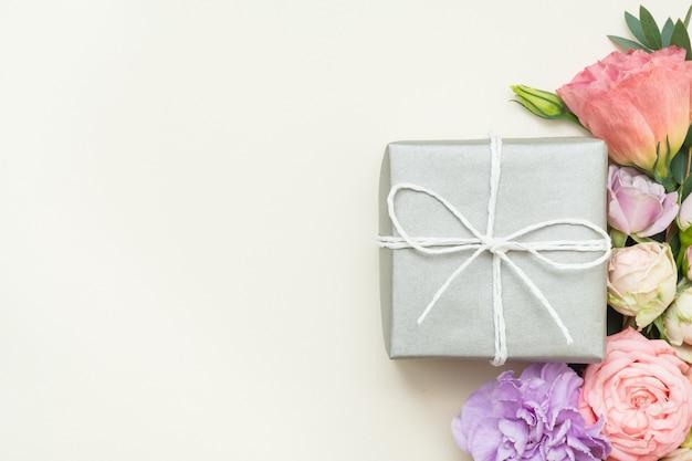 Présenter la livraison. boîte cadeau en argent. décor de fleurs festives. copiez l'espace sur fond ivoire.