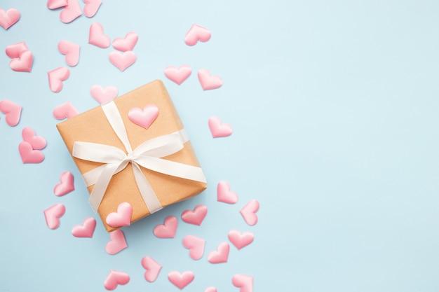 Présenter avec noeud blanc sur bleu avec des confettis coeur rose. style plat. saint valentin
