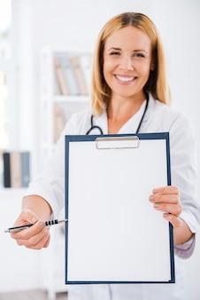 Présenter son avis médical. femme médecin souriante en uniforme blanc s'étendant sur le presse-papiers