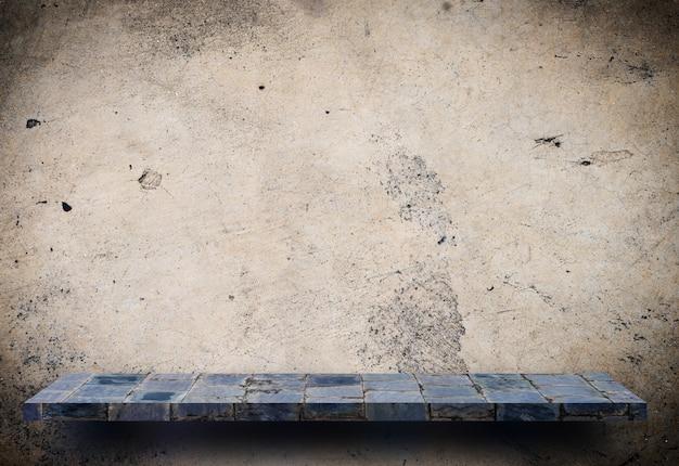 Présentoir de pierres grises sur un mur de ciment marron