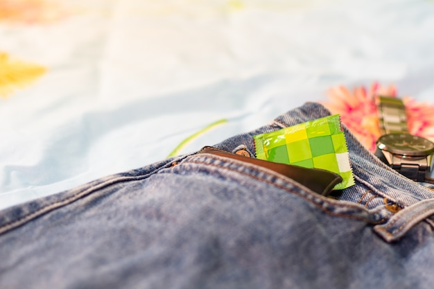 Préservatif et culotte avec un accessoire sur le lit