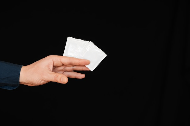 Préservatif dans l'emballage dans la main de l'homme