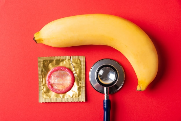 Préservatif en emballage, banane et stéthoscope médecin