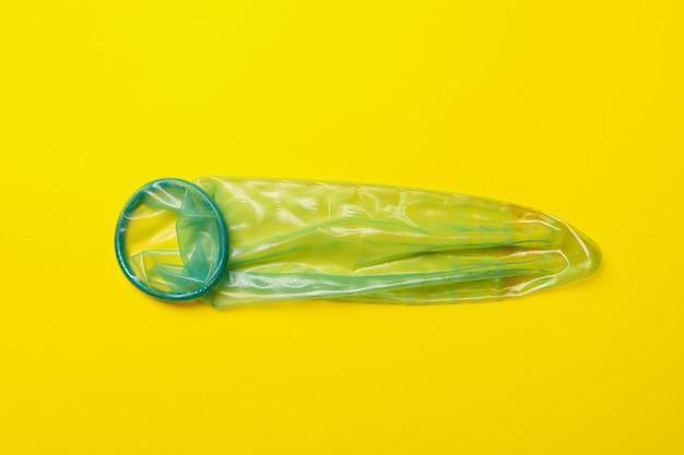 Préservatif à la menthe unique sur fond jaune, espace pour le texte
