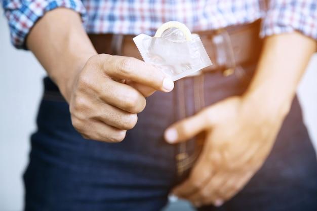 Préservatif prêt à l'emploi dans la main masculine.