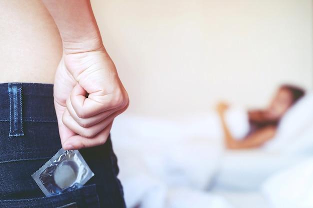 Préservatif prêt à être utilisé dans la main féminine, donnez le concept de sexe sans risque au préservatif sur le lit.