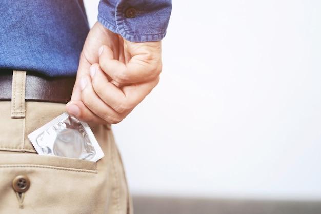 Préservatif prêt à être utilisé dans la main masculine, donnez le concept de sexe sans risque au préservatif sur le lit prévenir l'infection.