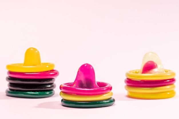 Préservatifs colorés sur fond rose