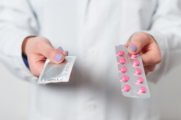 Préservatifs et contraceptifs entre les mains d'un médecin pour des rapports sexuels protégés