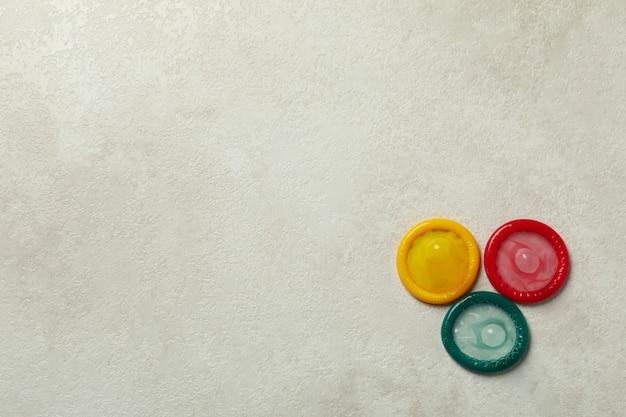 Préservatifs multicolores sur fond texturé blanc, espace pour le texte