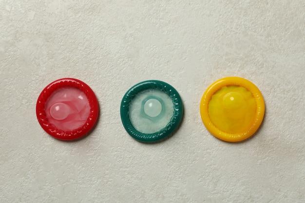 Préservatifs multicolores sur mur texturé blanc, vue du dessus