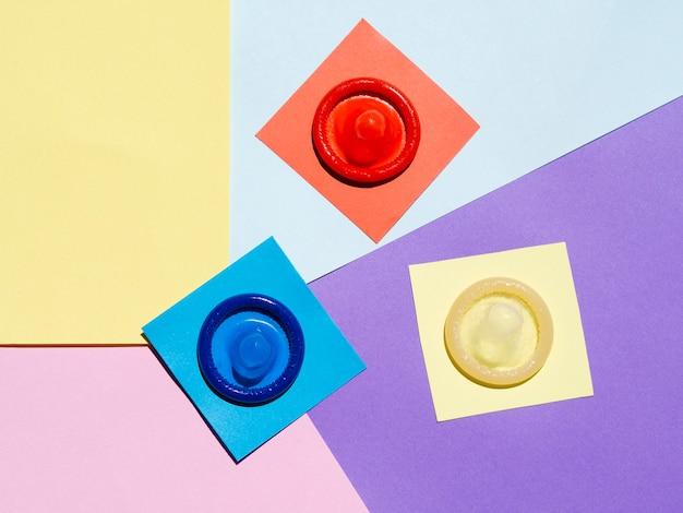 Préservatifs à plat sur fond coloré