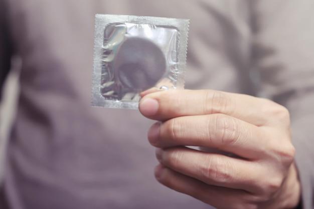 Préservatifs prêts à l'emploi dans la main de la femme, donnez le concept de sexe sûr au préservatif sur le lit. prévenez l'infection et les contraceptifs contrôlent le taux de natalité ou une prophylaxie sûre. journée mondiale du sida, laissez de l'espace pour le texte.