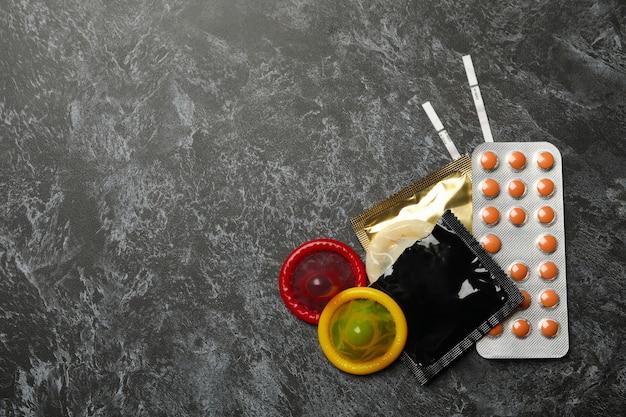 Préservatifs, tests de grossesse et pilules sur une surface fumée noire