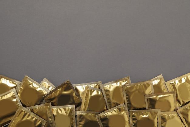 Préservatifs vierges sur fond gris, espace pour le texte