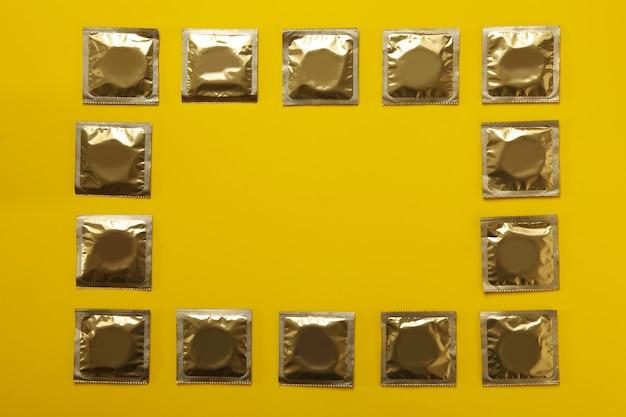 Préservatifs vierges sur fond jaune, espace pour le texte