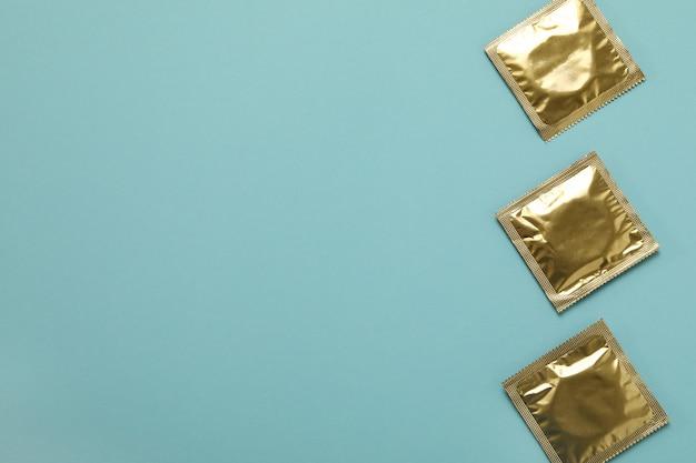 Préservatifs vierges sur mur bleu clair, espace pour le texte