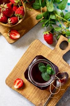 Préservation maison baies de fraises fraîches et sirop de fraises vue de dessus à plat