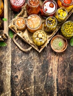 Préserve les aliments avec des légumes et des champignons sur un vieux plateau. sur un fond en bois.