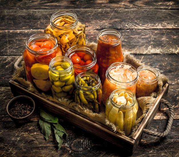 Préserve les aliments avec des légumes et des champignons sur un vieux plateau. sur une surface en bois.