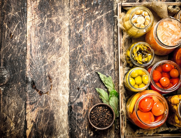 Préserve les aliments avec des légumes et des champignons sur un vieux plateau. sur une table en bois.