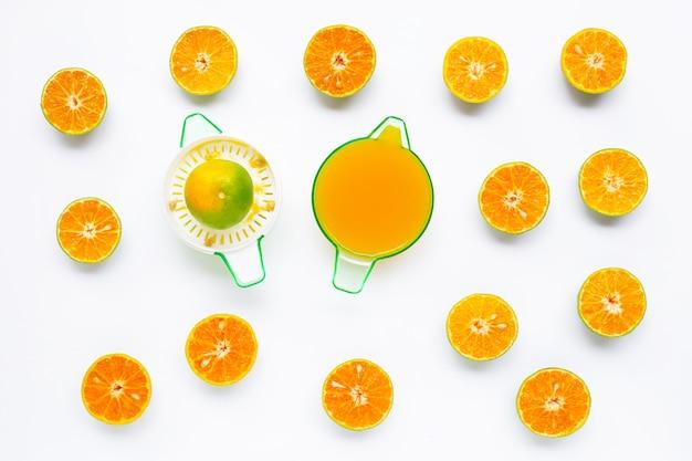 Presse-agrumes orange avec des oranges coupées en blanc sur blanc